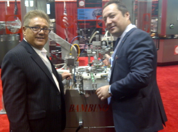 Alioscia Bassani, president of Capmatic, shows the Bambino filler and capper to Vito Pecoraro of Chanel.