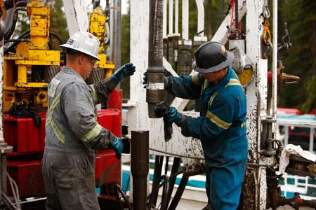 Workers change a drill bit in Kakwa, Alta. PHOTO Encana