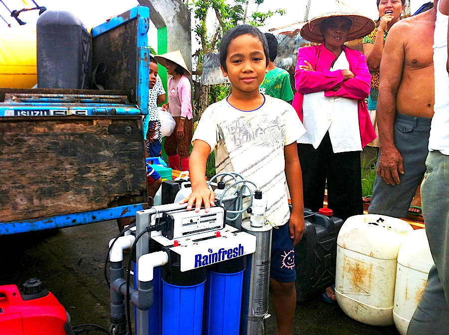 A Filipino boy with an AquaResponse unit after Typhoon Haiyan hit the Philippines in November 2013. The system purifies enough water to supply 20,000 people with safe drinking water daily. PHOTO Envirogard