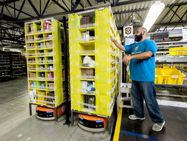 Amazon's squat orange robots slide under and transport shelves packed with product. PHOTO: Amazon.com Inc.