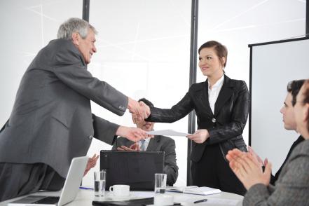 happy business leaders handshaking at meeting