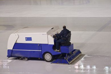 An ice resurfacer flooding the ice at an arena. The machine is often colloquially known as a Zamboni after the inventor and long-time industry leader. PHOTO: Myrabella, via Wikimedia Commons