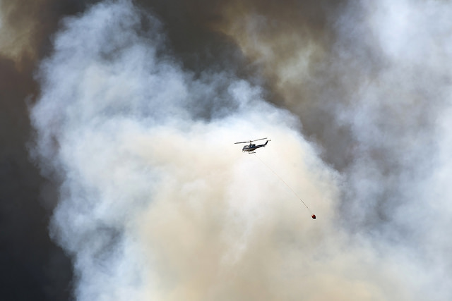 A helicopter carries fire retardant to the wildfire burning in a Fort McMurray neighbourhood on Wednesday, May 4, 2016. (photograph by Chris Schwarz/Government of Alberta)