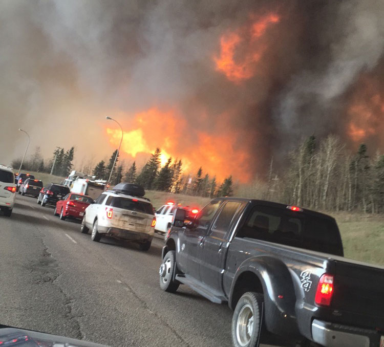 People fleeing flames from the Fort McMurray forest fire in the area of Highway 63 South. PHOTO: DarrenRD. CC-BY-SA-4.0
