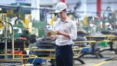 Man with clipboard in factory